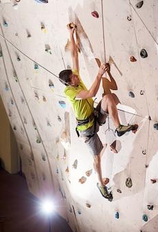 Homem praticando escalada em uma parede de pedra dentro de casa