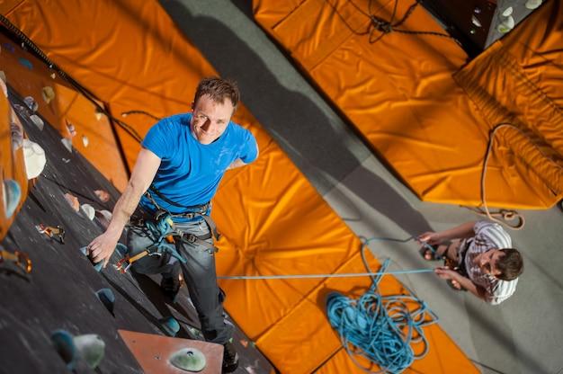 Homem praticando escalada na parede de pedra dentro de casa, olhando para a câmera, vista de cima