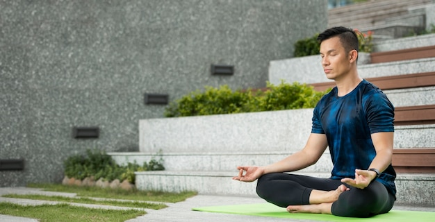 Homem praticando ioga ao ar livre com espaço de cópia