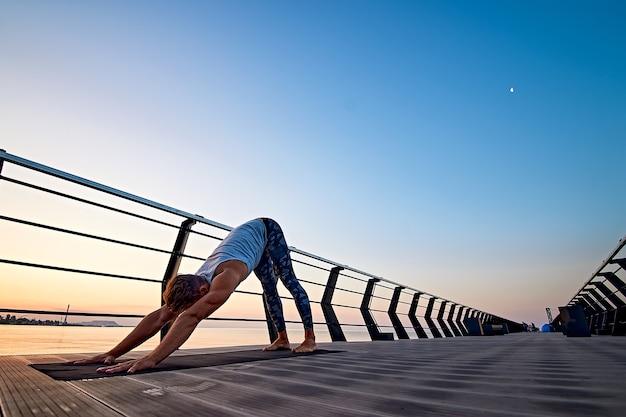 Homem praticando ioga ao pôr do sol e cachorrinho virado para baixo