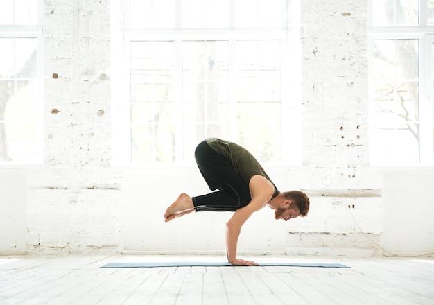 Homem praticando ioga avançada