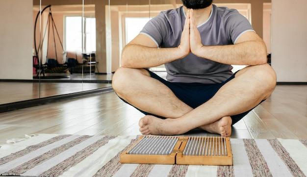 Homem praticando ioga, meditando, sentado com as mãos unidas no chão perto de uma placa de sadhu