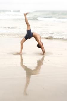 Homem praticando ioga na praia