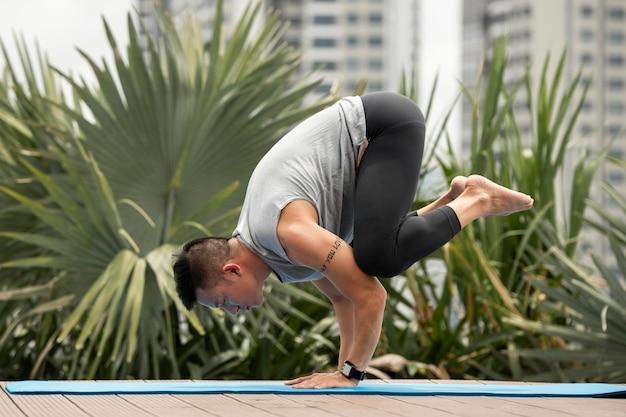 Homem praticando posição de ioga ao ar livre