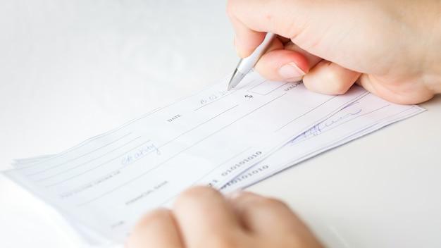 Homem preenchendo cheques bancários para pagamentos mensais e impostos.