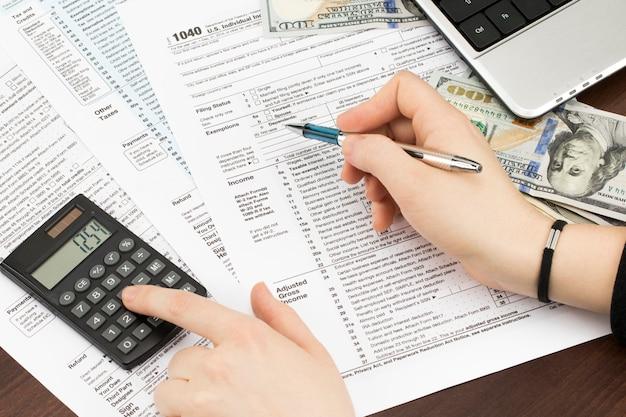 Homem preenchendo o formulário de imposto dos eua. formulário de imposto nos negócios renda escritório mão preencher conceito