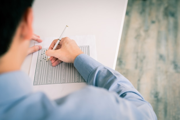 Homem preenchendo uma resposta na folha de respostas
