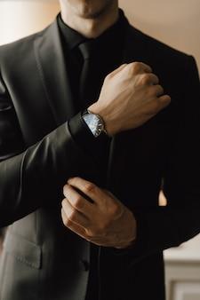 Homem prende um botão de punho em seu terno de negócio
