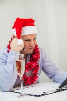 Homem preocupado calculando no fundo branco. o homem de negócios comemora o feliz natal e o boneco de neve do boneco de ano novo feliz