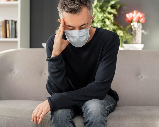 Homem preocupado com máscara no meio do tiro em consultório de terapia