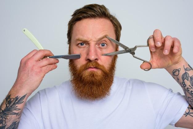 Homem preocupado com tesoura e lâmina está pronto para cortar a barba