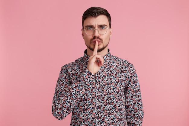 Homem preocupado de óculos com cabelos escuros barbudo em camisa colorida, demonstra um gesto de silêncio, secreto, segurando o dedo indicador perto da boca, isolado