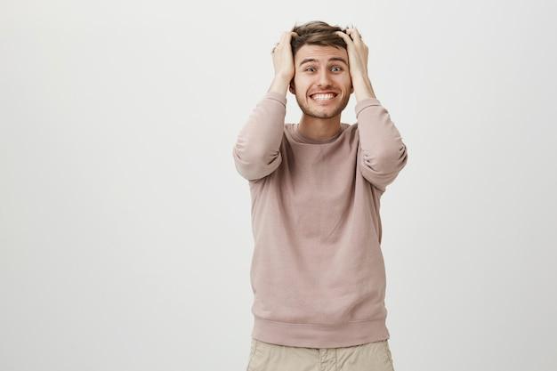 Homem preocupado e alarmado jogando o cabelo e cerrando os dentes em pânico