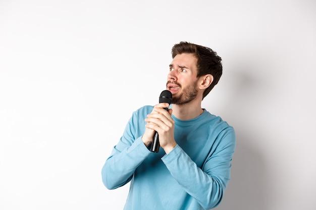 Homem preocupado e confuso lendo letras no karaokê, olhando para a esquerda com uma cara insegura, segurando o microfone e cantando, com fundo branco.