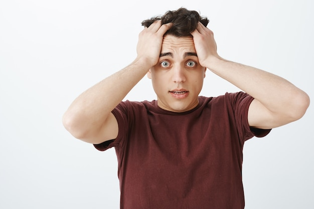 Homem preocupado e preocupado com uma camiseta vermelha, expressão frustrada