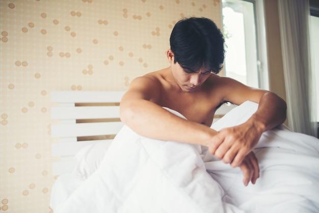 Homem preocupado sentado na cama de manhã, sério, pensando em algo