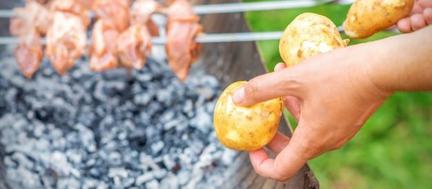 Homem prepara carne de churrasco com batatas