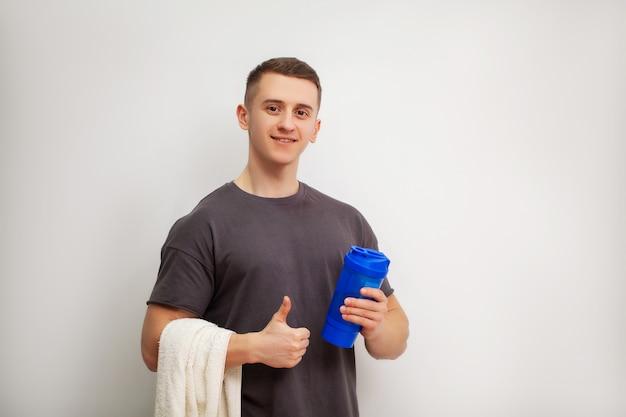Homem prepara um shake de proteína no shaker após o treino