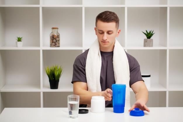 Homem prepara um shake de proteína no shaker após o treino.