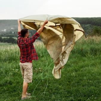 Homem preparando barraca para acampar