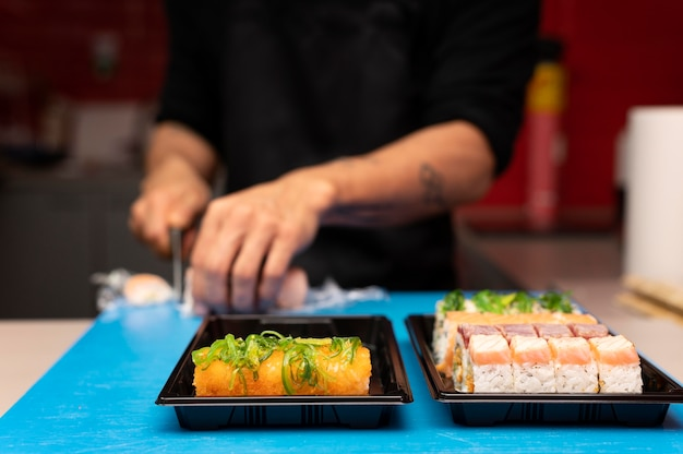 Homem preparando um pedido de sushi para levar