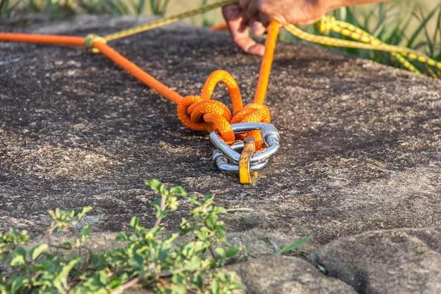 Homem preparando uma corda com mosquetão para rapel em uma montanha em teresópolis.