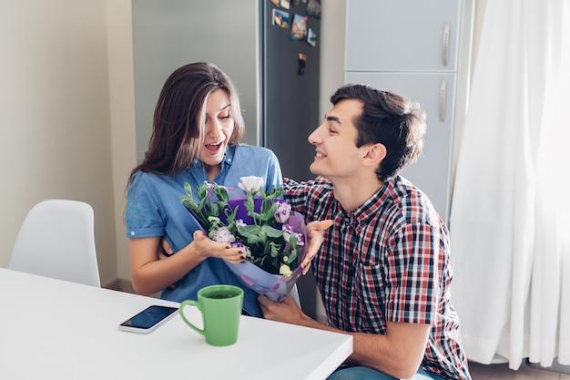 Homem presentear o buquê de flores para a namorada na cozinha em casa. surpresa romântica do dia dos namorados