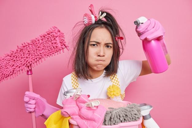 Homem pressiona os lábios parece cansado enquanto faz a limpeza de primavera segura o esfregão de garrafa dispensador limpa poses de quarto perto da cesta de lavanderia isolada em rosa