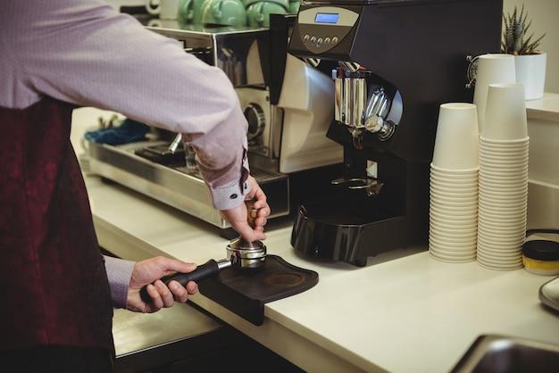 Homem pressionando café com tamper no porta-filtro