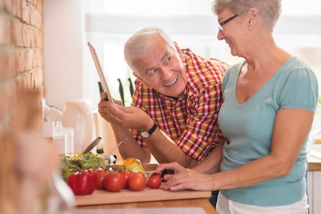 Homem prestativo e sua esposa preparando uma refeição saudável