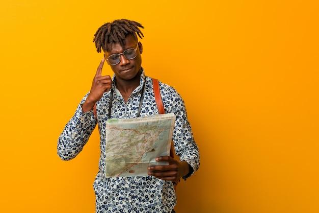 Homem preto novo do rasta que guarda um mapa que aponta seu templo com o dedo, pensando, focalizado em uma tarefa.