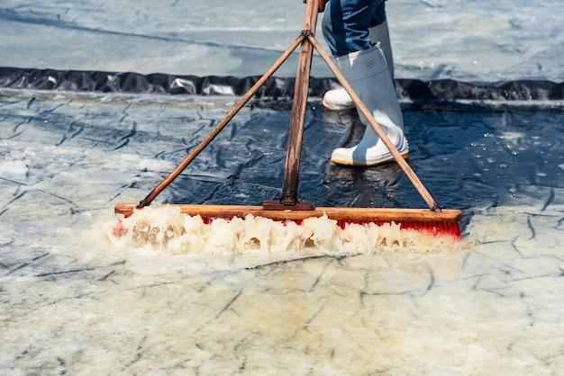 Homem processando grandes campos de sal junto com cristais de sal marinho, trabalho muito sob o sol em salinas de costas