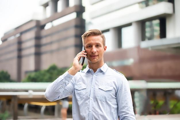 Homem profissional urbano novo que usa o telefone esperto. homem negócios, segurando, esperto móvel, telefone