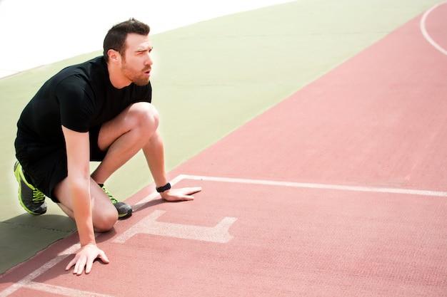 Homem pronto para correr na pista