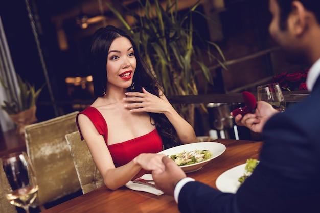 Homem propõe a mulher e dá-lhe um anel no restaurante.