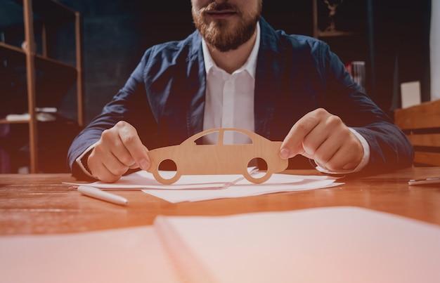 Homem propõe assinar uma apólice de seguro de carro, o agente está segurando o modelo de carro de madeira.