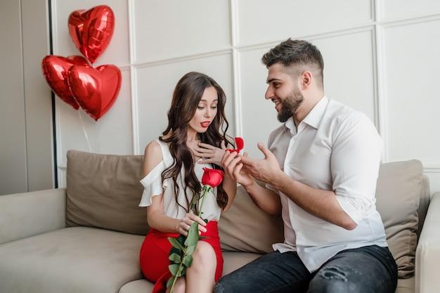 Homem propõe mulher com anel e rosa vermelha em casa no sofá com balões em forma de coração