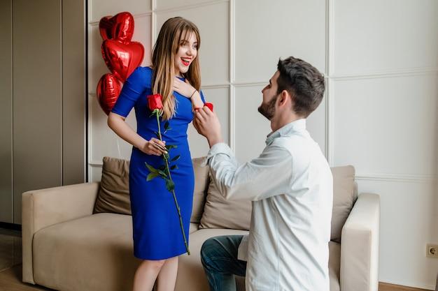 Homem propõe mulher com um anel e rosa vermelha em casa com balões em forma de coração