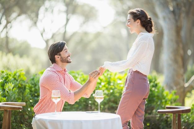 Homem propõe uma mulher com um anel no joelho