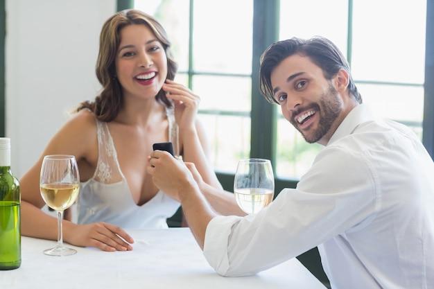 Homem propõe uma mulher com um anel no restaurante