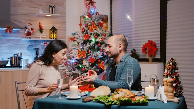 Homem propondo casamento com anel de noivado a mulher em jantar festivo