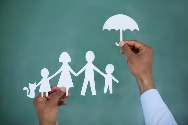 Homem protegendo papel cortado família com guarda-chuva