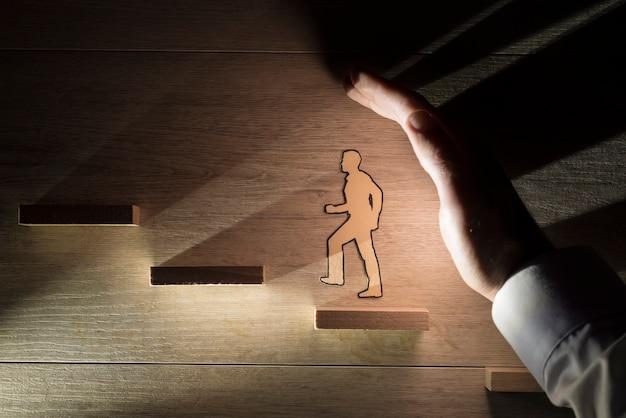 Homem protegendo um homem de papel durante o progresso ao subir escadas contra o espaço de madeira.
