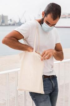 Homem próximo ao mar segurando bolsa e usando máscara facial