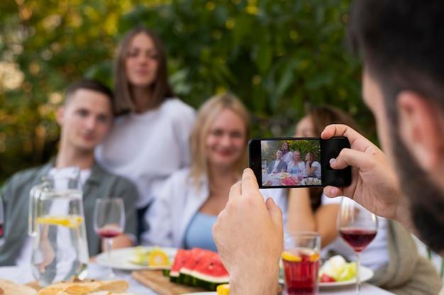 Homem próximo tirando fotos em grupo