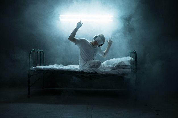 Homem psicopata vendado sentado na cama, horror da insônia, quarto escuro ... homem psicodélico tendo problemas todas as noites, depressão e estresse, tristeza, hospital psiquiátrico