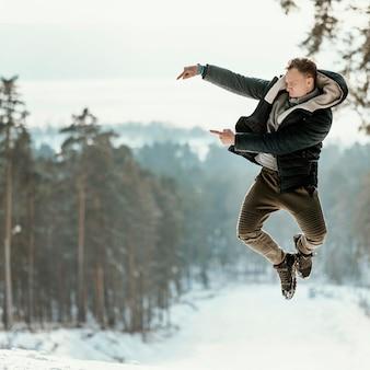 Homem pulando ao ar livre na natureza durante o inverno e apontando para o espaço de cópia