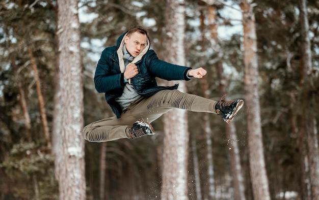 Homem pulando ao ar livre na natureza durante o inverno