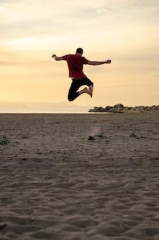 Homem pulando de alegria na praia está escurecendo Foto Premium