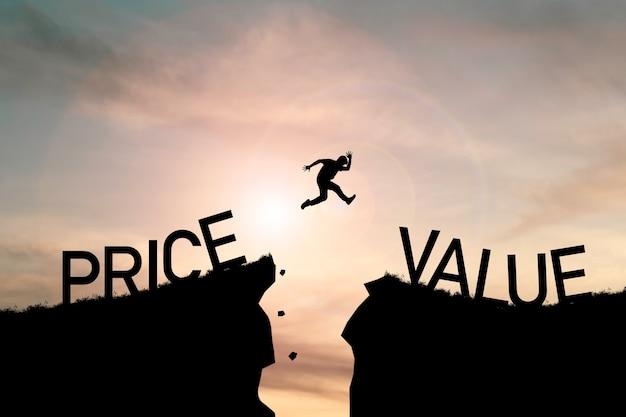 Homem pulando de penhasco de preço em penhasco de valor em céu nublado com luz do sol